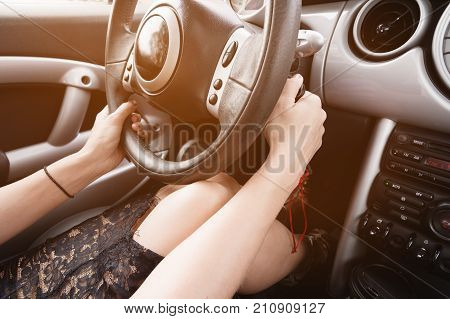 Closeup inside vehicle of hand holding key in ignition, steering wheel and black interior background, female driver concept