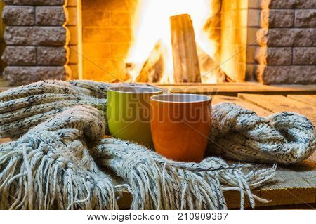 Two mugs for tea or coffee woolen things near cozy fireplace in country house winter vacation horizontal.