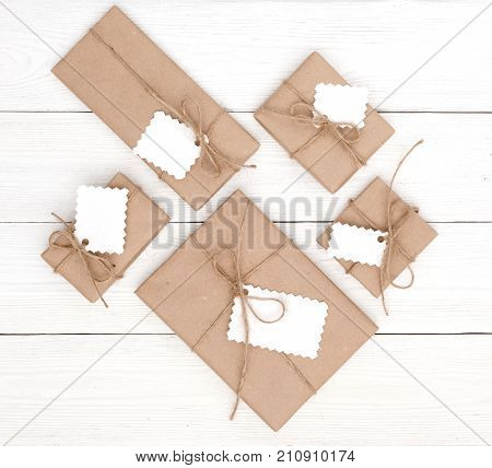Christmas gift or present boxes with tags on a white wooden table