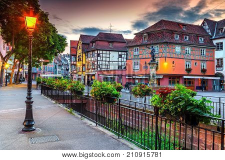 Spectacular colorful traditional French houses and decorated street with beautiful flowers, Colmar, France, Europe