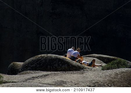 Meteora Greece - 9 October 2017: A man and two women resting and sunbathing on one of the rocks at the Meteora rock monastery complex in Greece