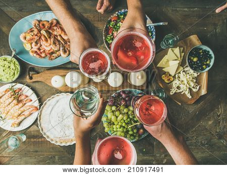 Holiday celebration table setting with food. Flat-lay of friends hands eating and drinking together. Top view of people having party, gathering, celebrating with rose champaign