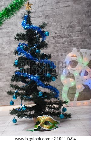 carnival mask under the Christmas tree. tree with blue balls.new year's masquerade