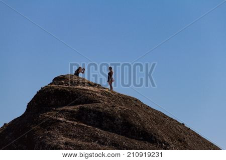 Meteora Greece - 9 October 2017: A man takes aphoto of a girl using a smartphone on top of a rock at Meteora monastery complex in Greece