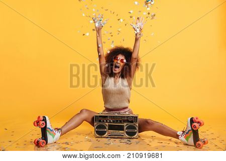 Emotional african disco woman in retro wear and roller scates throwing confetti while sitting with boombox, isolated on yellow background