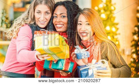 Group of three diversity women - white, black and Asian - with Christmas presents in a shopping mall in front of a Christmas tree