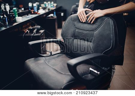 Barbershop. Armchair for hair cutting, hands of hairdresser in barber shop interior