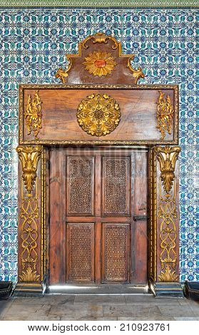 Cairo, Egypt - October 21, 2017: Closed wooden engraved aged door framed by golden ornate wooden frame on Turkish ceramic tiles wall with floral blue patterns Mosque of Manial Palace of Prince Mohammed Ali Tewfik Cairo Egypt