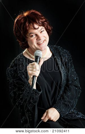 Female celebrity impersonator singing against a black background.