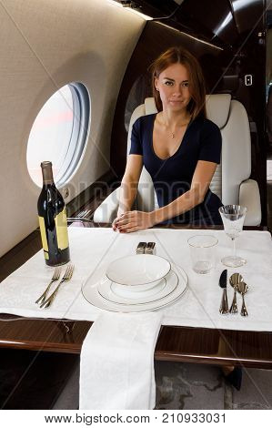 young beautiful woman in Luxury interior in bright colors of genuine leather in the business jet, sky and clouds through the porthole