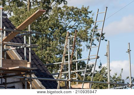 Scaffold pole platform with ladder attached to platform on new build country home. Scaffolding on house.