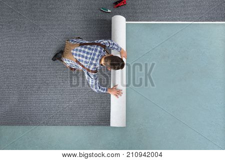 High Angle View Of Young Male Worker In Overalls Rolling Carpet On Floor At Home