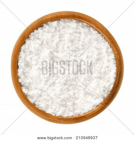 Powdered sugar in wooden bowl. Unsifted finely ground white refined sugar. Also called confectioners or icing sugar and icing cake. Isolated macro food photo close up from above on white background.