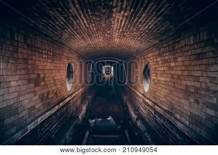 Red brick abandoned underground sewer tunnel with dramatic mysterious atmosphere, inside sewerage, dark toned