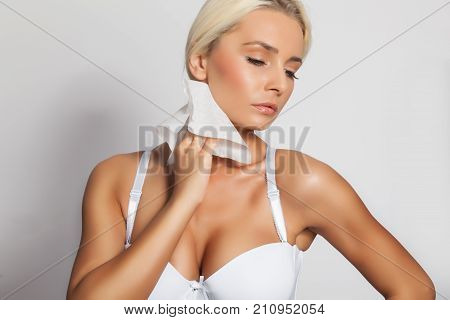 Young woman clean neck with wet wipes body breast lingerie