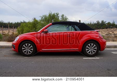 Costa Calma, Fuerteventura, Canary Islands, Spain - October 22, 2017: Red Volkswagen Beetle  cabrio parked by the side of the road in the city of Costa Calma. Nobody in de vehicle.