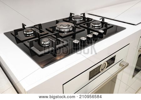 Gas stove with and embedded electric oven at brand new modern white kitchen