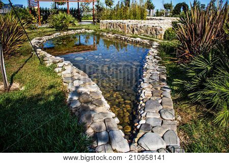 Charming garden pond lined with moss-covered stones wood and bushes. Pond equipped with water iris. In background garden sitting. Small natural garden lake in the spring.