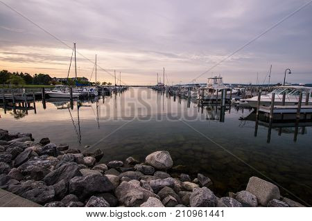 Boating Lifestyle. Boats docked in a marina with a rocky foreground and the beginning of a sunset in the background.