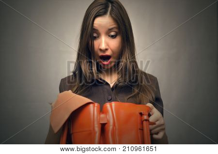 Young business woman in dress with a wide open mouth looks into the bag she holds in her hands and in shocked from she saw inside. Not enough money to buy. Perplexed Woman forgot her wallet at home.