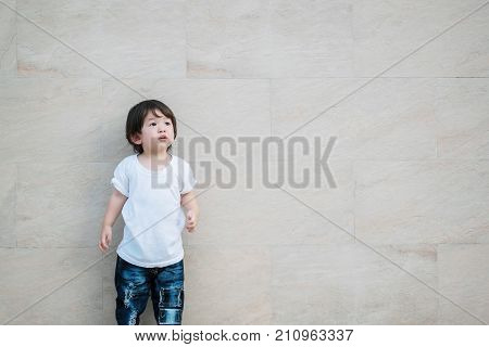 Closeup cute asian kid look at the space on marble stone wall textured background