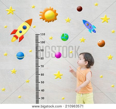 Closeup happy asian kid stand and point to scale of measure height with cute cartoon at the marble stone wall textured background in growth of kid concept