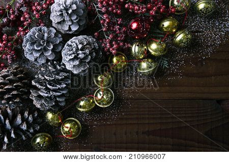 Jingle bells, pine cones and red berries on a rustic wood table with snow. Horizontal format with copy space.