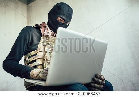 Terrorist is using a computer to perform a security drill fighter from an abandoned house.