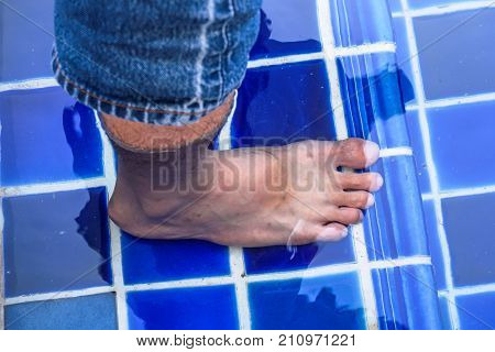 Men's feet stand in the pool.