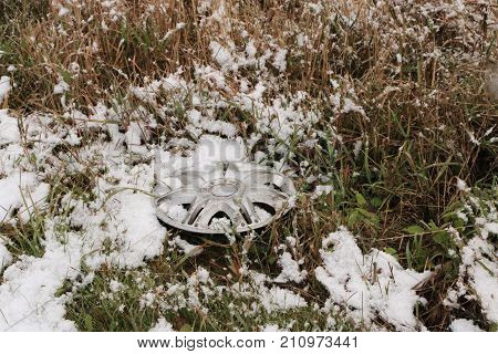 Hubcap Silvery Lies On The Roadside In A Grass Covered With Snow
