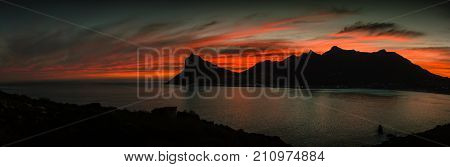 Mountain peak silhouetted against the red sky of sunset with a calm ocean in the foreground.  The Sentinel Peak, Hout Bay, South Africa