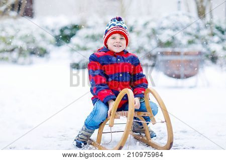 Little kid boy holding a sledge a sledge. School child playing outdoors and have fun in winter during snowfall.