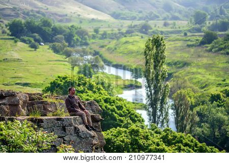Traveler sits on the edge of abyss above vast forest territory and summer mountains