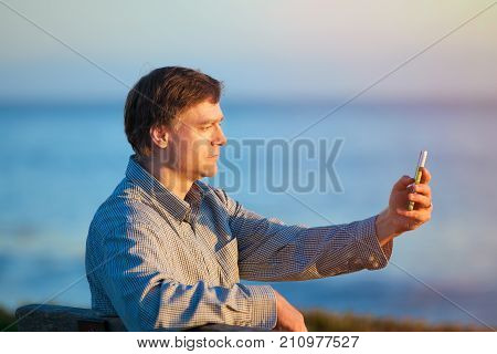 Handsome Caucasian businessman in early fifties sitting on park bench outdoors by ocean using cellphone near sunset