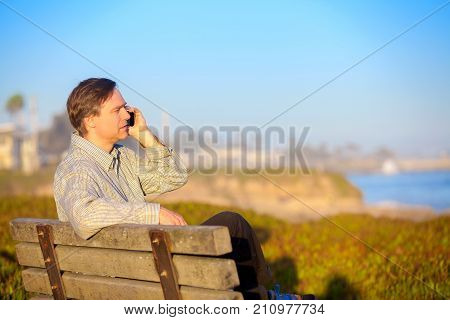 Handsome Caucasian businessman in early fifties sitting on park bench outdoors by ocean talking on cellphone near sunset