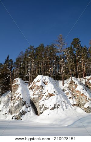 Snow-covered nameless cliffs on the shore of icy Chusovaya river. Ural, Russia.