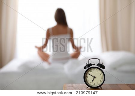 Alarm clock standing on bedside table has already rung early morning to wake up. Woman do yoga in bed in background. Early awakening, healthy lifestyle contemplation concept..