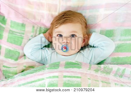 Adorable little baby girl after sleeping in bed. Calm peaceful child with a pacifier or dummy.