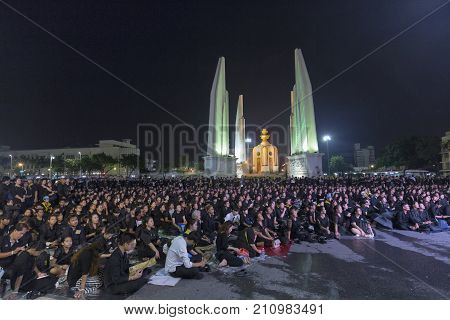 BANGKOK THAILAND - OCTOBER 26: Unidentified mourners in black sit and watch the royal activities for the cremation of Rama 9 the former king next to Democracy Monument in Bangkok Thailand on October 26 2017.