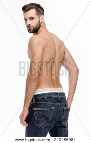 Sexy back. Rear view of young shirtless man in jeans looking at camera while standing against white background.