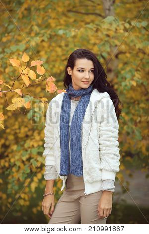 Autumn girl walking in city park. Fall woman portrait of happy lovely and beautiful mixed race Asian Caucasian young woman in forest in fall colors. Model in white casual clothes looking away