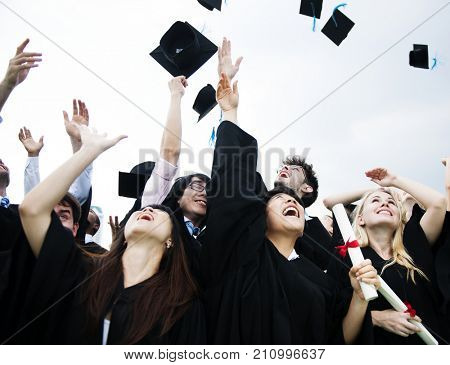 Group of diverse grads throwing caps up in the sky