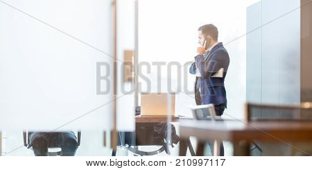 Businessman talking on a mobile phone while looking through modern corporate office window, holding financial newspaper.