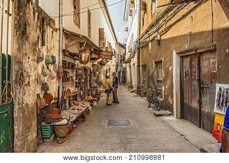 STONE TOWN, ZANZIBAR - OCTOBER 24, 2014: Tourists on a typical narrow street in Stone Town. Stone Town is the old part of Zanzibar City, the capital of Zanzibar, Tanzania.