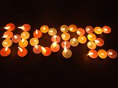 Spelling of word hope with bright lighted candles on a black background poster