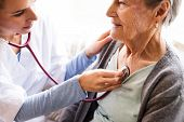 Health visitor and a senior woman during home visit. A nurse or a doctor examining a woman. Close up. poster