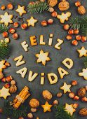 FELIZ NAVIDAD COOKIES. Words Merry Christmas en Spanish with baked cookies Christmas decoration and nuts on black slate background. Christmas card for hispanic countries top view. poster