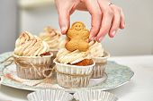 Christmas Treats. Handmade cookies, cupcakes, confection standing on the table.  Female hands decorating cupcakes using gingerbreads. Christmas and New Year. poster