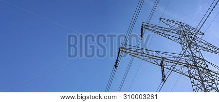 Looking Up Steel Power Pylon Construction With High Voltage Cables Against Blue Sky. Wide Banner For
