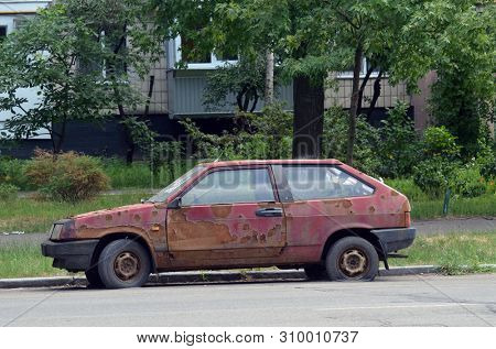 Abandoned car in the city. Modern ghetto. Bad district. Residential area in Kiev at summer. Exterior.July 5, 2019. Kiev,Ukraine